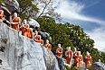 Statues of Buddhist Monks queuing to take lotus flower offerings to Buddha