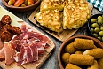 Traditional spanish tapas: Croquettes, olives, omelette, ham and patatas bravas